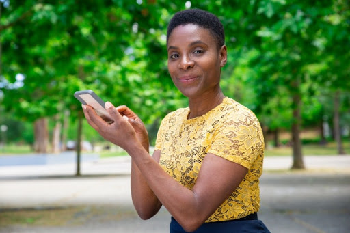 Mulher usando o celular com acessórios para aparelho auditivo