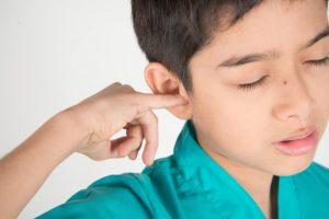 Menino com coceira no ouvido
