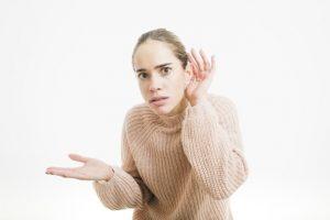 Mulher com perda auditiva e mão no ouvido