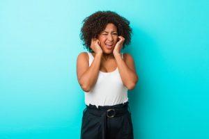 Pessoa sente sintomas que podem indicar uma perda auditiva.